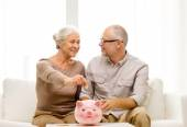 Senior couple with money and piggy bank at home — Stock Photo