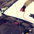 Closeup of man under bonnet with starter cables — Stock Photo #56373443