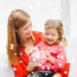 Mother and daughter with piggy bank — Stock Photo #56375311
