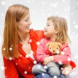Mother and daughter with teddy bear toy — Stock Photo #56375625