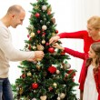 Smiling family decorating christmas tree at home — Stock Photo #56378567