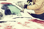 Closeup of man scraping ice from car — Stock Photo