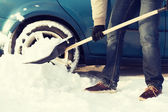 Closeup of man digging up stuck in snow car — Stock Photo