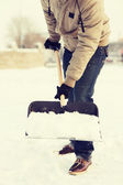 Close-up do homem cavar a neve da calçada — Fotografia Stock