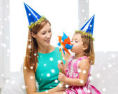 Mother and daughter in party hats with pinwheel — Stock Photo