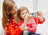 Smiling mother and daughter with camera — Stock Photo