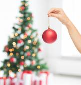 Close up of woman in sweater with christmas ball — Stock Photo