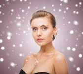 Woman wearing shiny diamond earrings and pendant — Stock Photo