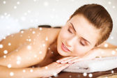 Woman in spa salon with hot stones — Stock Photo