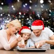 Happy family in santa helper hats cooking — Stock Photo #56583705