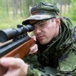Close up of soldier or hunter with gun in forest — Stock Photo #56585805