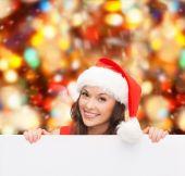Vrouw in helper kerstmuts met een leeg wit bord — Stockfoto