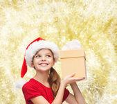 Smiling girl in santa helper hat with gift box — Stock Photo