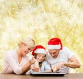Happy family in santa helper hats cooking — Stock Photo