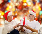 Happy senior couple in santa hats with gift box — Foto Stock