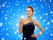 Smiling woman in evening dress holding credit card — Stockfoto