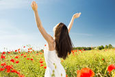 Young woman on poppy field — Stock Photo