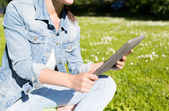 Close up of girl with tablet pc sitting on grass — Stock Photo