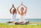 Smiling couple making yoga exercises outdoors — Stock Photo