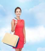 Uśmiechający się z torby na zakupy i kart plastikowych — Zdjęcie stockowe