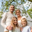 Happy family in front of house outdoors — Stock Photo #56672395