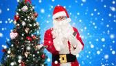санта клаус со смартфоном и рождественской елкой — Стоковое фото