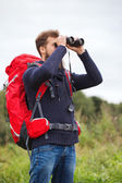 Man with backpack and binocular outdoors — Stockfoto