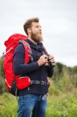 Smiling man with backpack and binocular outdoors — Foto de Stock