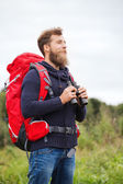 Smiling man with backpack and binocular outdoors — Stockfoto