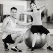 Male trainer with woman doing crunches on the ball — Stock Photo #56749297
