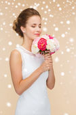 Smiling woman in white dress with bunch of flowers — Stock Photo
