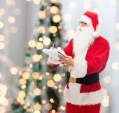 Man in costume of santa claus with notepad — Stok fotoğraf
