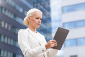 Businesswoman working with tablet pc outdoors — Stock Photo