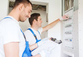 Builders with clipboard and electrical panel — Stock Photo