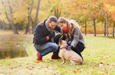 Smiling couple with dog in autumn park — Photo