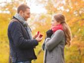 Smiling couple with engagement ring in gift box — ストック写真