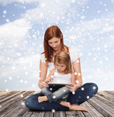 Happy mother with little girl and tablet pc — Stock Photo