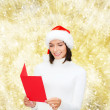 Smiling woman in santa hat with greeting card — Stock Photo #56932049
