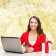 Smiling woman with credit card and laptop — Stock Photo #56933453