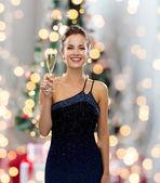 Usmívající se žena hospodářství sklenici šumivého vína — Stock fotografie