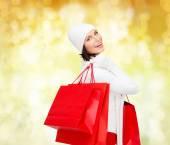 Souriante jeune femme avec des sacs à provisions rouges — Photo