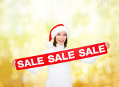 Smiling woman in santa helper hat with sale sign — Foto de Stock