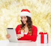Smiling woman in santa hat with gift and tablet pc — Stock Photo