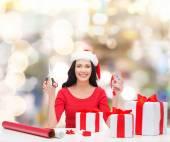 Lächelnde frau in nikolausmütze helfer packen geschenke — Stockfoto