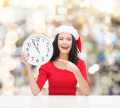 Smiling woman in santa helper hat with clock — Stock Photo