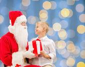 微笑的小男孩与圣诞老人和礼物 — 图库照片