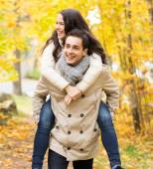 Smiling couple having fun in autumn park — Stock Photo