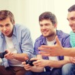 Smiling friends playing video games at home — Stock Photo #57216405