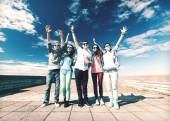 Group of teenagers holding hands up — Stock Photo