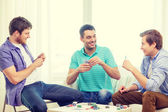 Happy three male friends playing poker at home — Stock Photo